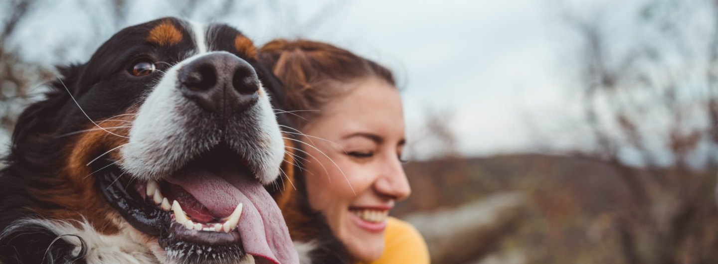 woman hugging large dog and smiling