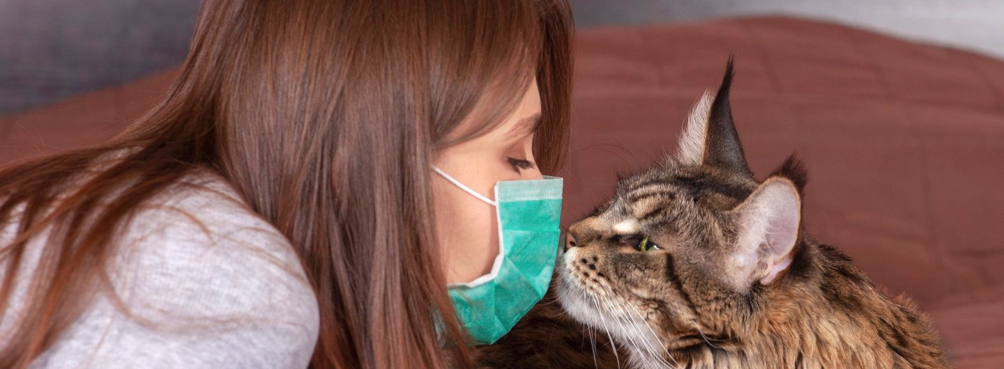 woman wearing mask holding her face up to cat