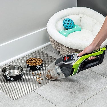 Bissell BOLT Cordless Hand Vac cleaning up mess next to dog food bowl