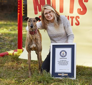Feather the dog and her owner posing with award for highest jump