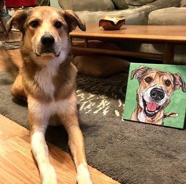 dog lying next to his custom portrait