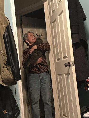 person holding cat in doorway