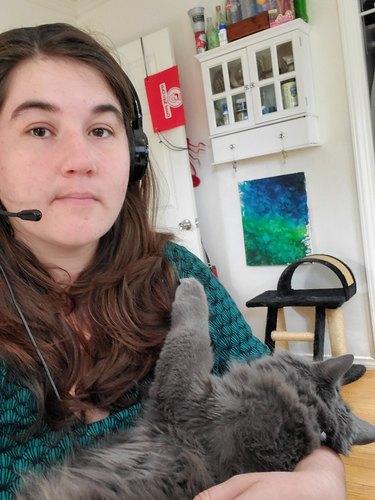 teacher cradles cat during online lecture