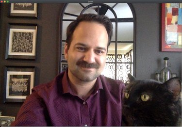 cat sits on professor's lap during online class