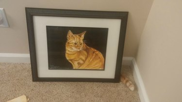 Cat sitting behind a painting of itself with just its tail visible