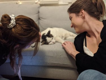 Two women fawning over a sleeping cat.