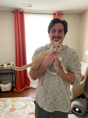 man poses picture with kitten