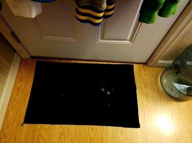 black cat sleeping on black rug