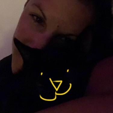 woman adds filter to black cats face so it's visible in picture