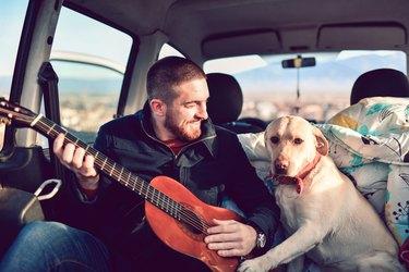 man playing guitar next to dog in van