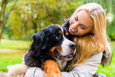 Woman embracing her dog in autumn park