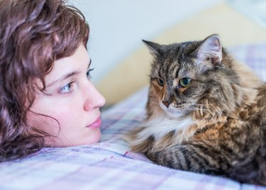Young woman looking at maine coon cat on bed