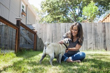 Woman playing with pug while sitting on grassy field in backyard