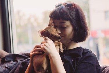 Girl holding her puppy Miniature Pinscher