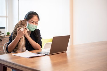 Beautiful young Asian woman using computer for video call meeting with friends at home during coronavirus pandemic for self isolation and social distancing.