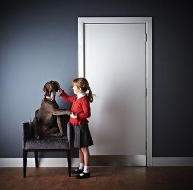 Little girl standing with dog outside vets door