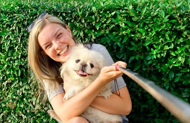Beautiful girl with dog taken pictures of her self.