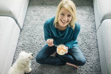 Portrait of happy woman with dog eating fruit yoghurt in living room