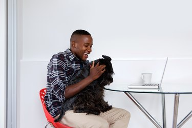 Young african guy playing with his pet dog