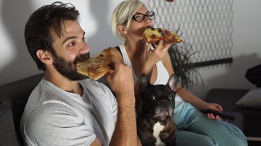 Man and woman have pizza for dinner with pup