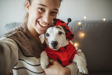 woman posing with small dog in ladybug costume