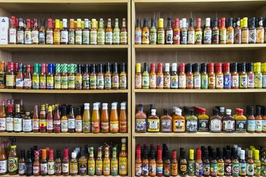 Jars of hot sauce on shelves in store