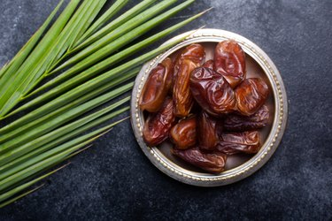 Dish of dates next to palm leaf