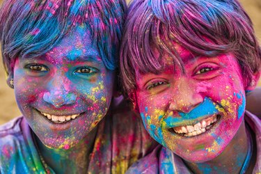 Group of happy Indian boys playing holi, desert village, India