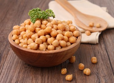 Wooden bowl overflowing with chickpeas topped with parsley