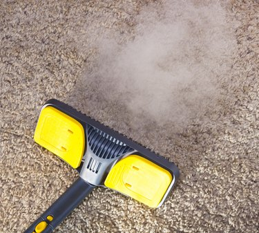 Close-up of dry steam cleaner cleaning a carpet