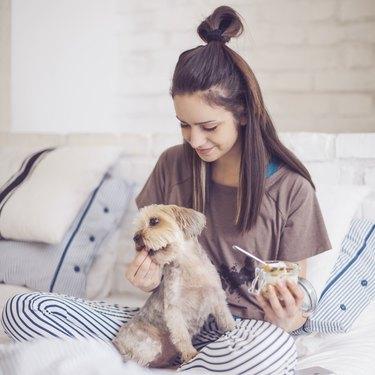 woman at home eating yogurt and holding dog
