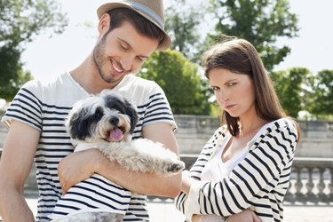 Man carrying a puppy and smiling with a woman looking sad, Paris, Ile-de-France, France