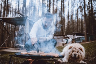 Handsome Male Flipping Barbecue Meat While Dog Drools