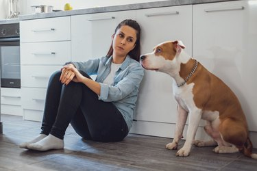 Sad woman sitting on a kitchen floor with her dog
