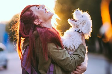 Attractive Redheaded Girl and White Puppy Smiling Together