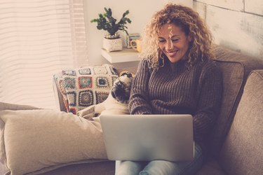 beautiful blonde curly woman working at home with a laptop internet connected while her best friends creamy pug look at the screen to check the work - friendship and lovely puppy concept