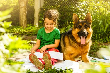 Little girl reading a book with her friend puppy dog in the outdoors.