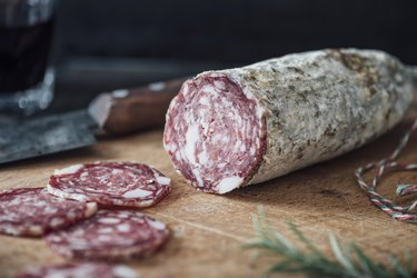 Sliced salami on cutting board