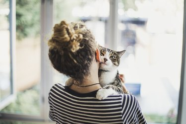 A teenage girl holding her cat