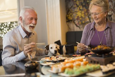 Senior couple eating sushi with their dog at the table