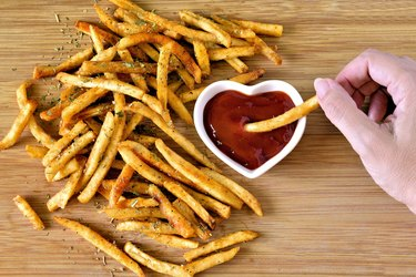 French fries and ketchup, person dipping one fry in ketchup