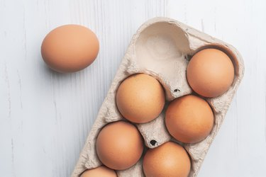 fresh eggs in paper tray on white surface