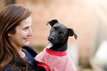 Woman holding a black dog wearing a sweater