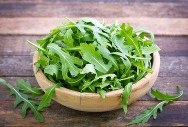 Fresh arugula salad in wooden bowl