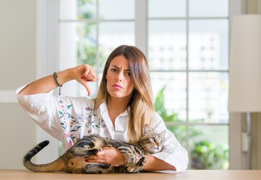 Young woman at home playing with her cat with angry face, negative sign showing dislike with thumbs down, rejection concept