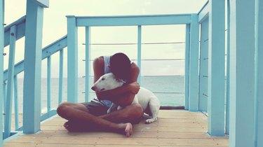 Man Embracing Dog On Pier