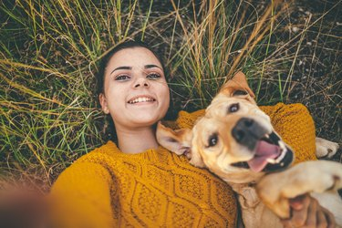 woman laying on grass with happy dog