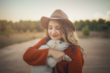 Love woman embracing pet dog in nature