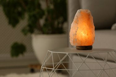 Himalayan salt lamp on table against blurred background