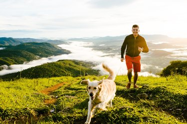 Young Man And Dog Running On Mountain Against Cloudy Sky